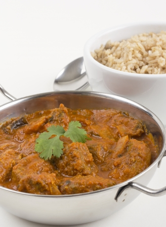 Meat madras served with pilau rice on a white background.