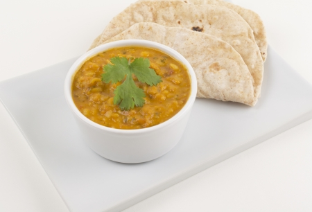 Tarka Dahl and chapatis on a white background. Stock Photo
