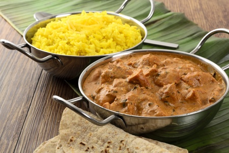 indian meal: Butter Chicken & Lemon Rice - Indian butter chicken curry and lemon rice served with chapatis on a banana leaf.
