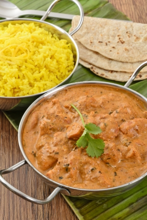 Butter Chicken   Lemon Rice - Indian butter chicken curry and lemon rice served with chapatis on a banana leaf   photo