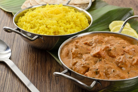 indian meal: Butter Chicken   Lemon Rice - Indian butter chicken curry and lemon rice served with chapatis on a banana leaf