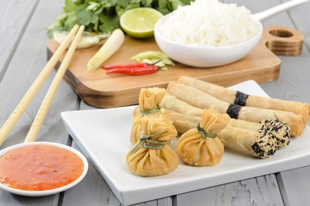 oriental food: Oriental Snacks - Asian appetisers  wontons and spring rolls served with sweet chilli sauce  Cooking ingredients and rice on the background