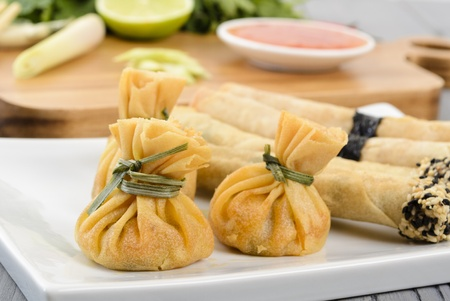 appetisers  wontons and spring rolls served with sweet chilli sauce  Cooking ingredients and rice on the background   photo
