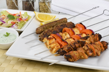pakistani pakistan: Kebabs - Selection of chicken tikka, paneer tikka and seekh kebabs served with crunchy salad, mint raita and lemon wedges