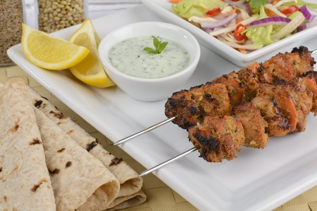 pakistani pakistan:  Chicken Tikka Kebab - Tandoori chicken kebabs on metal skewers served with mint raita, crunchy salad, lemon wedges and chapatis