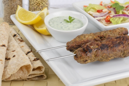 Seekh Kebab - Seekh Kebab - Minced meat kebabs on metal skewers served with mint raita, crunchy salad, lemon wedges and chapatis