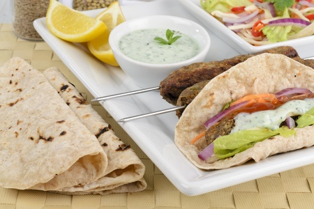 Seekh Kebab - Minced meat kebabs on metal skewers and as a wrap served with chili sauce, mint raita, crunchy salad, lemon wedges and chapatis