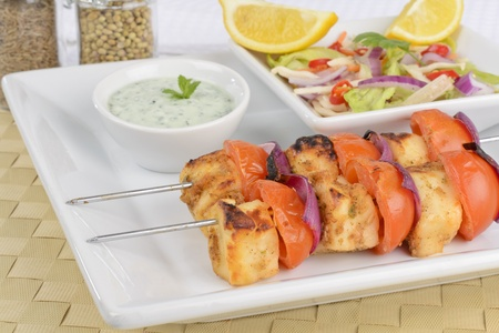 Paneer Tikka Kebab - Tadoori indian cheese skewers with tomato and red onions served with chrunchy, salad mint raita and lemon wedges Stock Photo