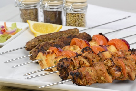 Kebabs - Selection of chicken tikka, paneer tikka and seekh kebabs served with crunchy salad and lemon wedges  photo