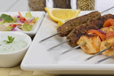 Kebabs - Selection of paneer tikka and seekh kebabs served with crunchy salad, mint raita and lemon wedges