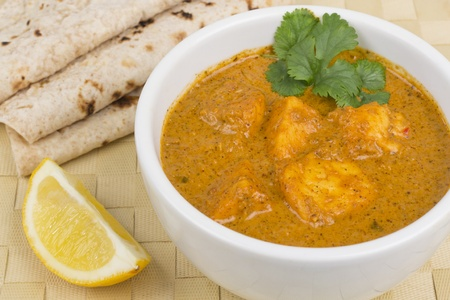 pakistani food: Paneer Makhani or Shahi Paneer  Paneer Butter Masala  - Indian curd cheese curry served with chapatis and a wedge of lemon