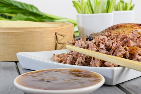 hoisin sauce: Peking Duck - Chinese roast duck served with pancakes, cucumber, spring onions and hoisin   plum sauce  Close-up - Shallow depth of field and focus on chopsticks   Stock Photo