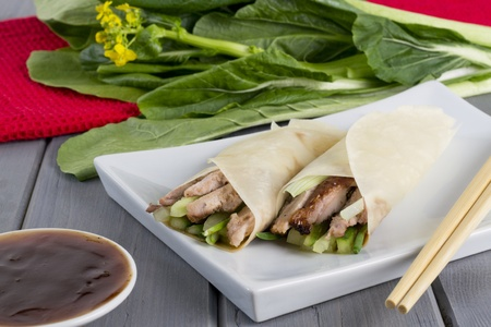 Peking Duck - Chinese peking duck wrapped in pancakes with cucumber, spring onions and hoisin sauce  Stock Photo