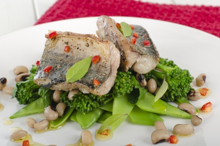 Grilled Mackerel - Pan fried fresh mackerel fillet on a bed of green vegetables and black eyed beans, drizzled with red chilli, lime and olive oil dressing