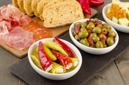 Cold Tapas - Spanish style antipasti and bread  soft cheese stuffed chilies, green olives and sun-dried tomatoes and cheese cubes with herbs  Lomo, spicy chorizo and serrano ham slices   Stock Photo