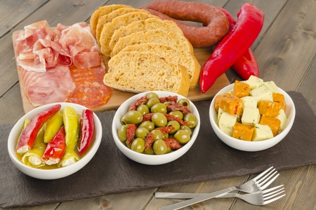 Cold Tapas - Spanish style antipasti and bread  soft cheese stuffed chilies, green olives and sun-dried tomatoes and cheese cubes with herbs  Lomo, spicy chorizo and serrano ham slices   photo