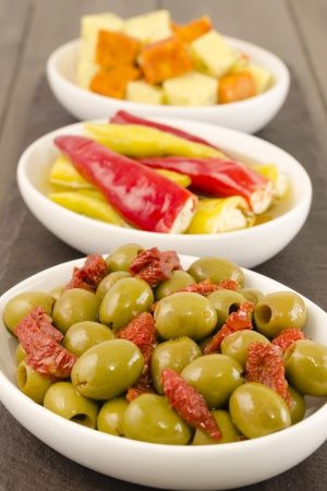Cold Tapas - Spanish style antipasti with green olives and sun-dried tomatoes, soft cheese stuffed chilies, and cheese cubes with herbs  photo