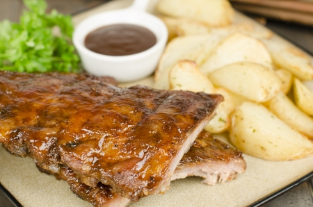 BBQ Ribs - Marinated pork ribs with potato wedges and barbeque sauce  Stock Photo
