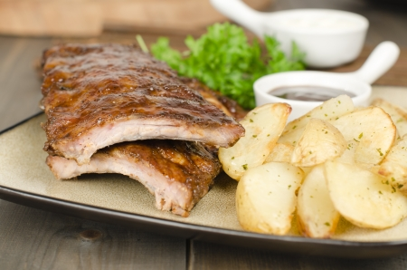 BBQ Ribs - Marinated pork ribs with potato wedges and barbeque sauce  photo