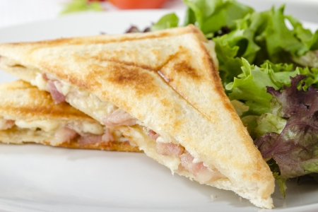 Bacon   Cheese Toastie served with salad on a white background  Close up
