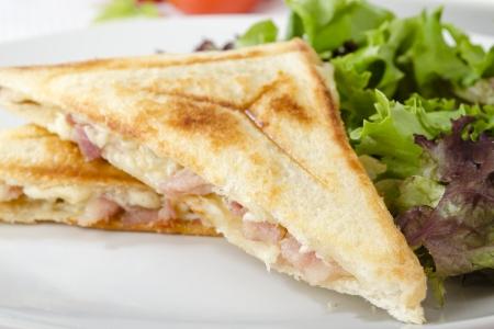 Bacon Fromage Toastie servi avec de la salade sur un fond blanc Gros plan