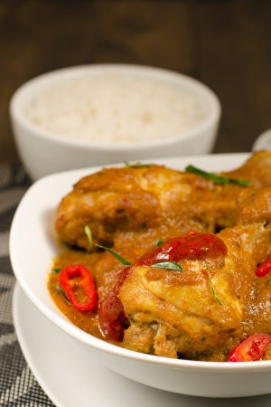 Ayam Kari Kapitan - Malaysian spicy chicken curry with coconut milk served with sticky rice  Traditional Nyonya cuisine  Low key lighting  Close up  Stock Photo