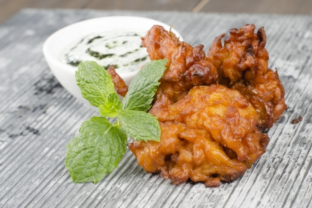 Onion Bhajis   Dips - Deep fried south asian snack with mint raita and garnished with mint leaves on a slate