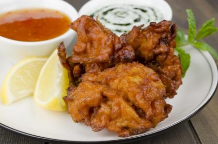 Onion Bhajis Dips - casse-cro�te frits sud asiatique avec la sauce chili et la menthe Raita, garni de feuilles de menthe sur une plaque