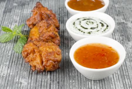 Onion Bhajis Dips - frit du sud asiatique casse-cro�te avec sauce chili, la menthe raita et chutney � la mangue, garnie de feuilles de menthe sur une ardoise Banque d'images