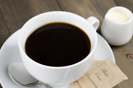 kopi: Americano black coffee in a white cup with raw demerara sugar sachets and a jug of milk  Close up  Stock Photo