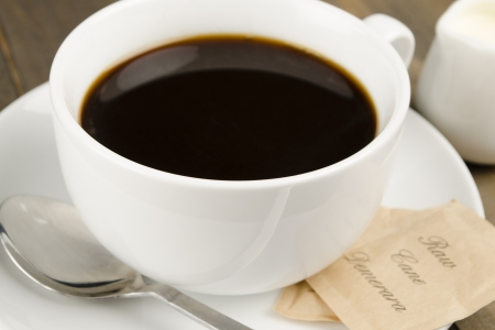 Americano black coffee in a white cup with raw demerara sugar sachets and a jug of milk  Close up  Reklamní fotografie