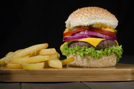 black sesame: Cheeseburger and Chips on a black background  Low key lighting