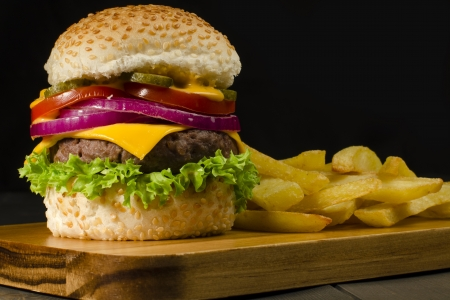 Cheeseburger and Chips on a black background  Low key lighting Stock Photo - 15532167