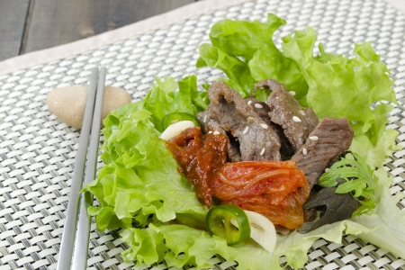 Beef Bulgogi - Korean marinated BBQ beef served in lettuce leaf with Kimchi Stock Photo - 15532251
