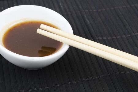 soy sauce: Hoisin   Chopsticks - Close up of chopsticks resting on a small white bowl of asian dipping sauce on a black mat
