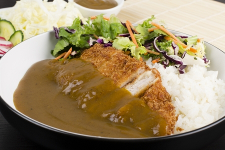 Katsu Kare - Japanese breaded deep fried pork cutlet  tonkatsu  served with shredded cabbage, salad, steamed rice and curry sauce  Stock Photo