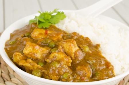 curry: Curry de Pollo chino con guisantes y cebolla servido con arroz al vapor Foto de archivo