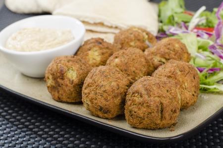 Falafel - boules de pois chiches frits servis avec du tahini, salade et pain pita