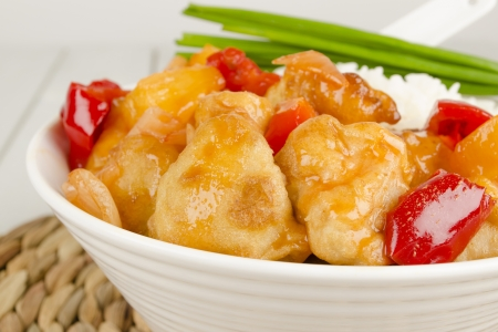 Sweet and Sour Chicken with pineapple and red bell peppers served with steamed rice photo