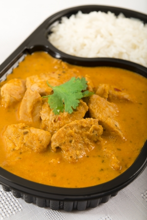 Takeaway curry - Chicken curry and rice in a plastic container garnished with coriander photo