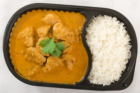 Para llevar curry - Curry de pollo y el arroz en un recipiente de pl�stico con guarnici�n de cilantro photo