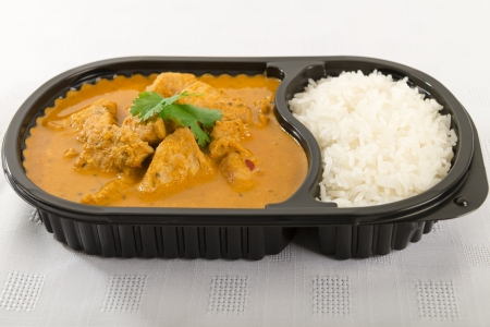 Takeaway curry - Chicken curry and rice in a plastic container garnished with coriander