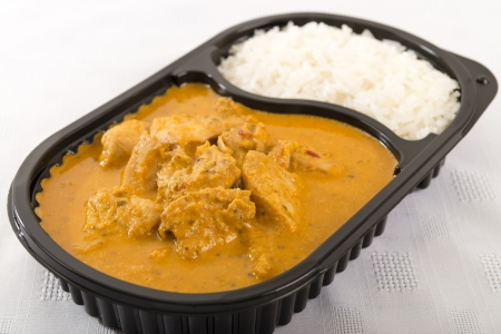 Takeaway Curry - Chicken curry with coconut milk and plain rice in a plastic container on a white background  Stock Photo