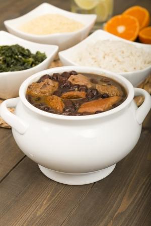Feijoada - Br�sil rago�t de haricots boeuf, saucisse, viande de porc et noir servi avec de la farine de manioc, choux, riz blanc et Caipirinha oranges sur le fond Comfort Food Banque d'images