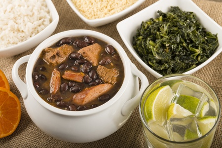 Feijoada - Brazilian beef, sausage, pork and black bean stew served with manioc flour, kale, white rice and oranges  Caipirinha drink on the side  photo
