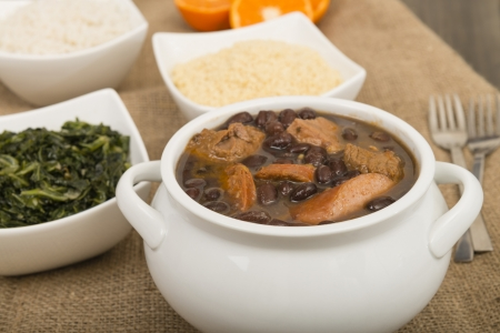 Feijoada - Brazilian beef, sausage, pork and black bean stew served with manioc flour, kale, white rice and oranges