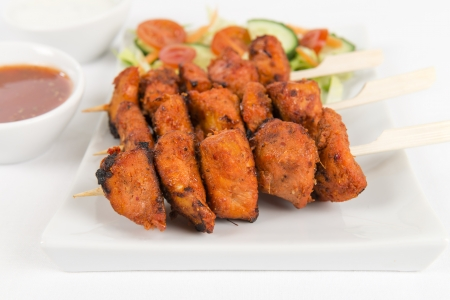 Chicken Tikka Kebab - Tandoori chicken tikka skewers served with salad, chili sauce and mint and yogurt raita on a white background  photo