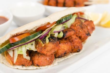 Chicken Tikka Wrap - BBQ Tandoori chicken tikka with salad in a pitta bread on a white background  Stock Photo