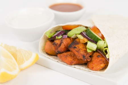 Chicken Tikka Wrap - Tandoori chicken tikka with salad wrapped in a flatbread, served with chili sauce, yogurt and mint raita and lemon wedges on a white background  photo