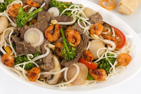 Chow Mein - Chinese Stir-fried noodles with beef, shrimp and vegetables served with sring rolls, prawn crackers and dipping sauce on a white background  Stock Photo - 17050413